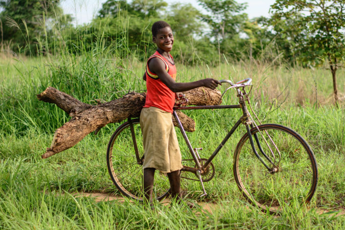 An African boy carries firewood on teh back of his bicycle rack.