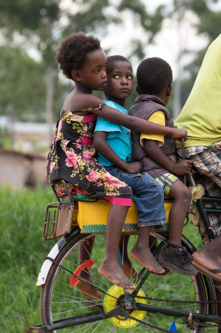 African kids pester each other while siting on the back rack of a bicycle taxi.