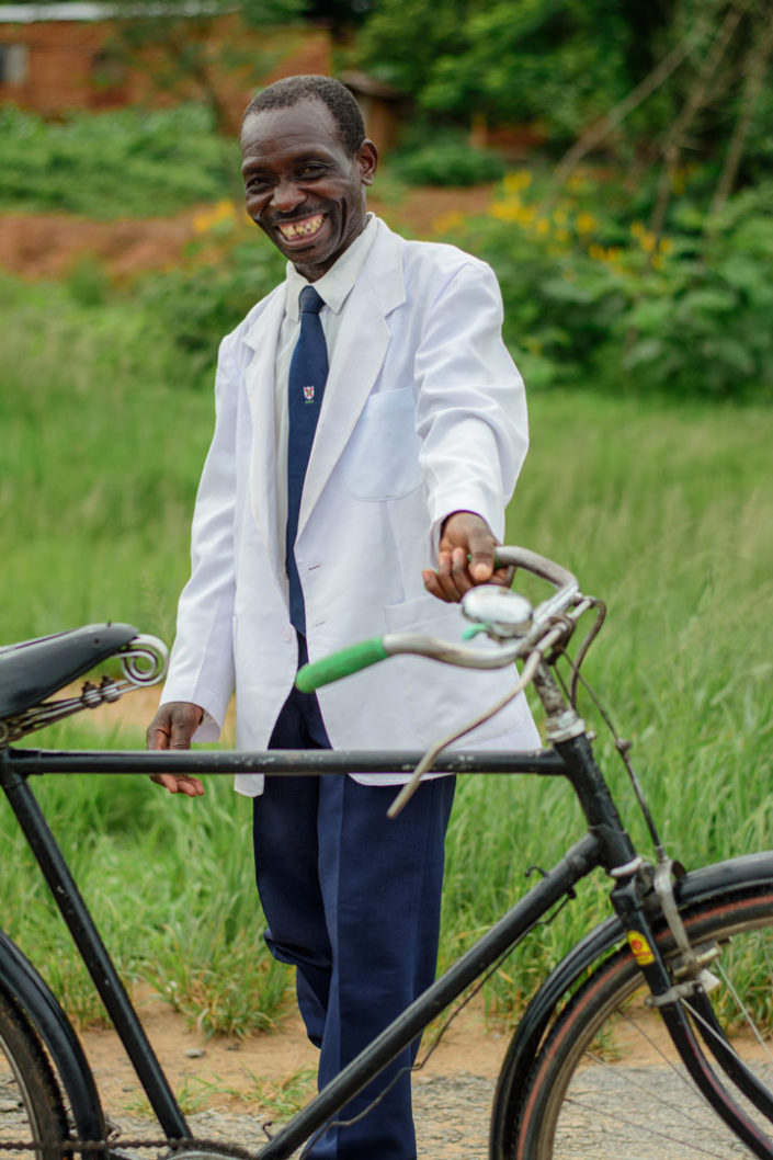A respectably dressed man stands in front of a bicycle in africa