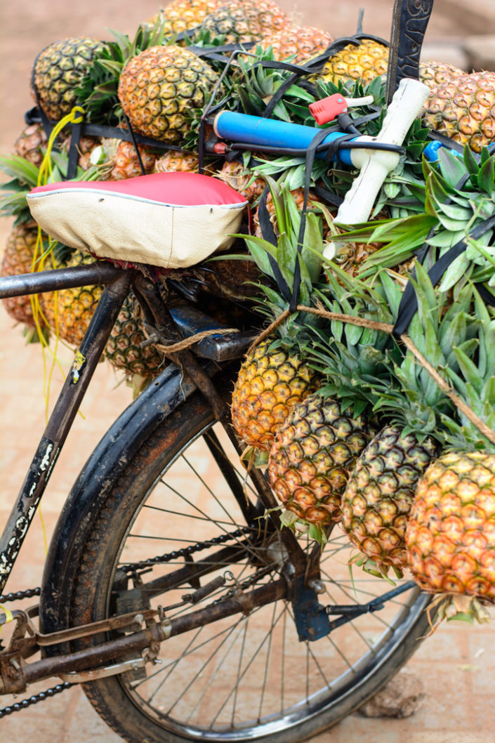 The rear rack of a bicycle in Africa is loaded up with pineapples.