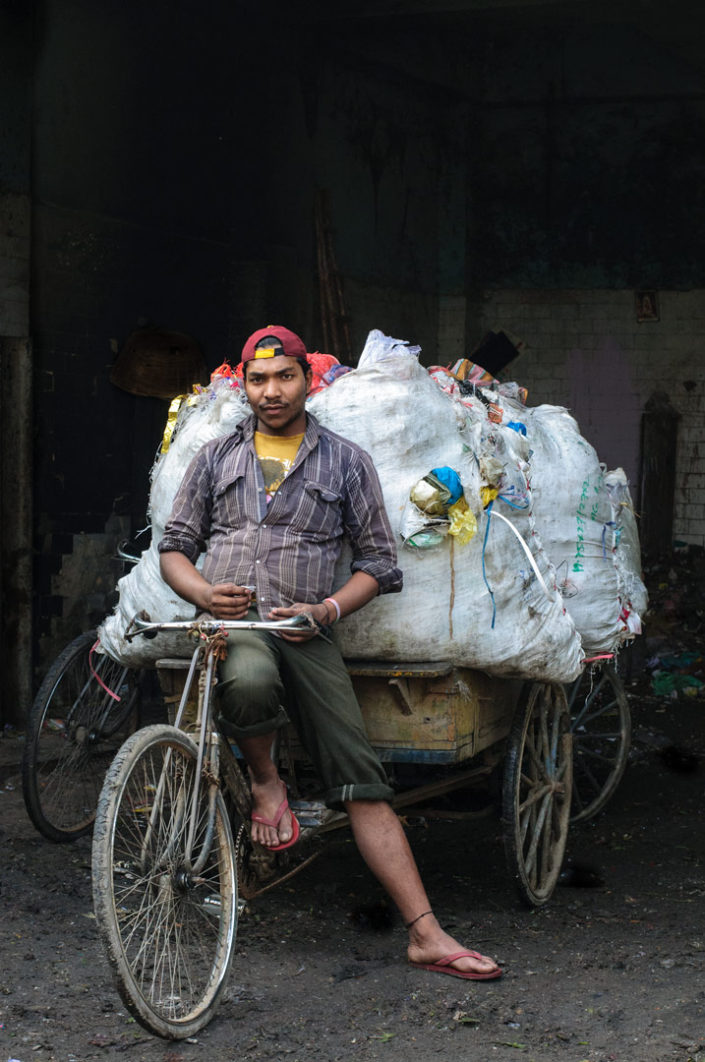 A rickshaw is loaded with recycle material in India.