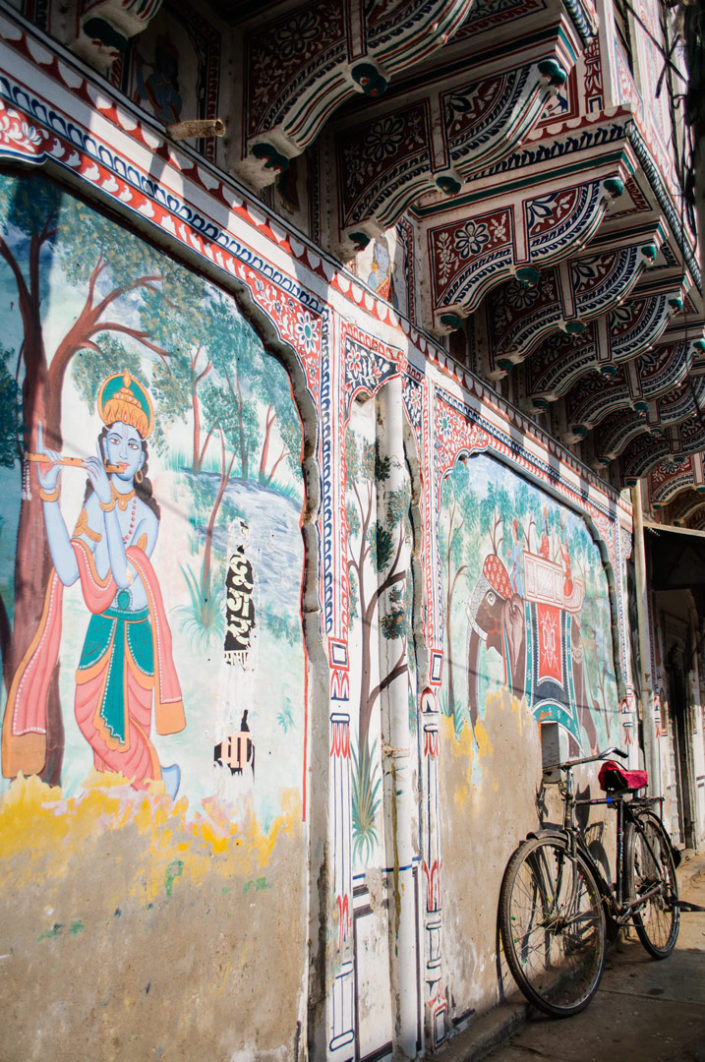A bicycle is leaned against a painted wall in the Shekhawati region of India.