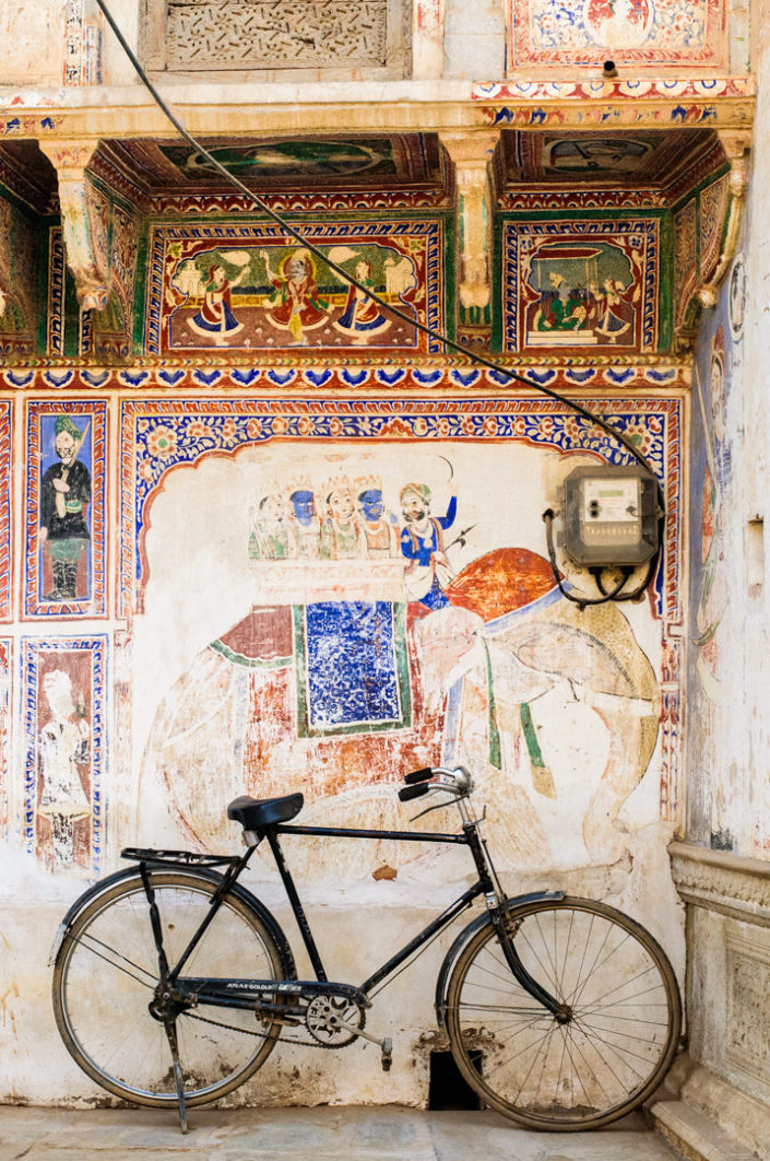 A bicycle is parked against a wall mural in North India