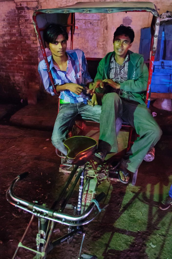 Two men sit in an Indian rickshaw.