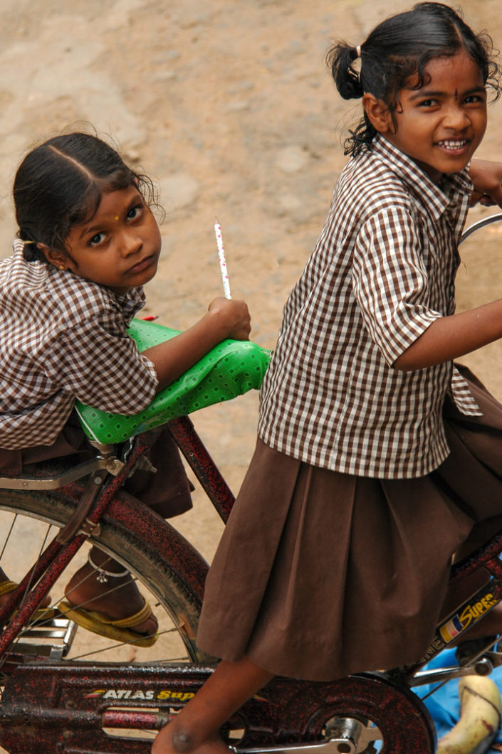 Indian schoolgirls sit on a bicycle