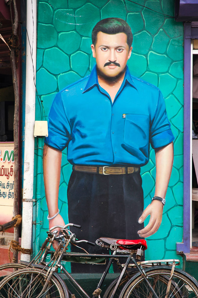 Bicycles are leaned against a portrait of a man in India