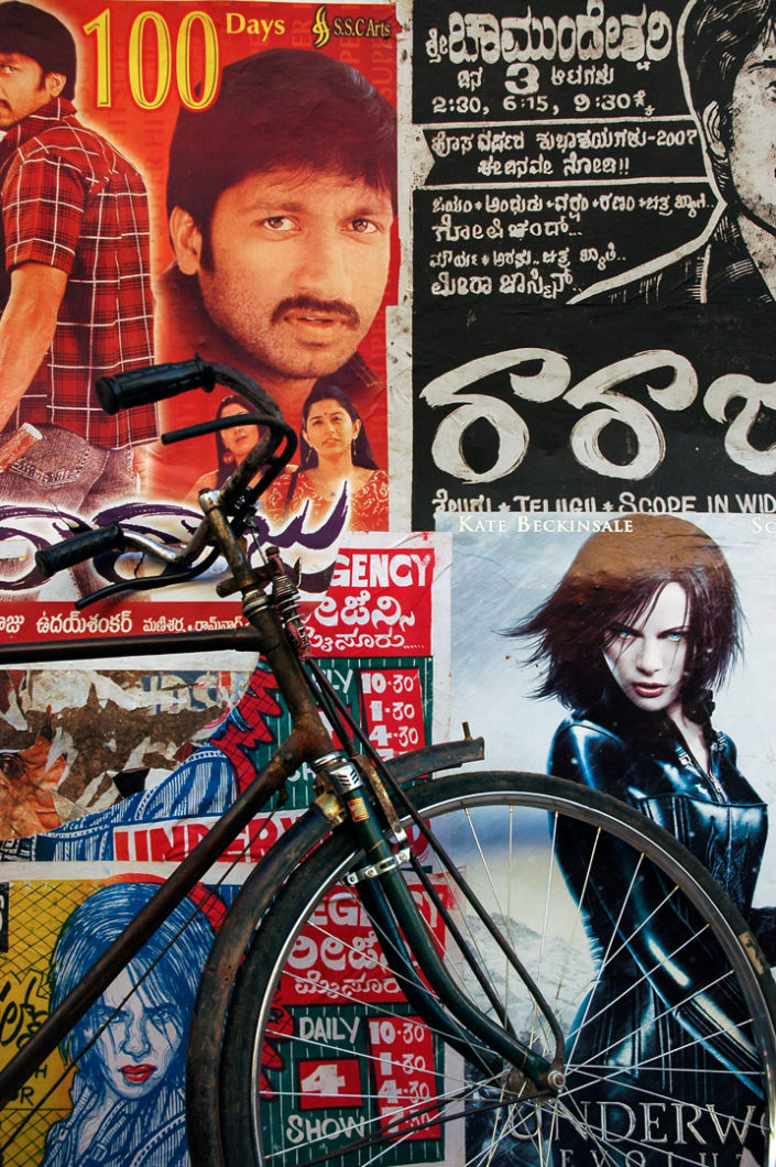 An Indian bicycle is leaned against movie posters