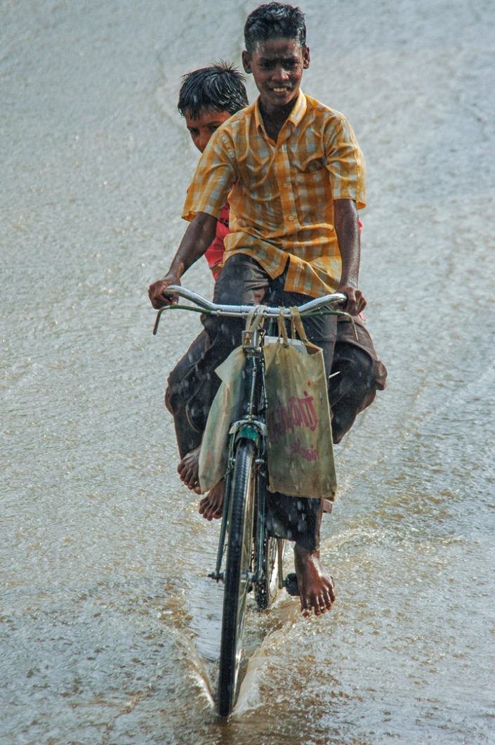 Indian boys enjoy riding a bike through a flooded street