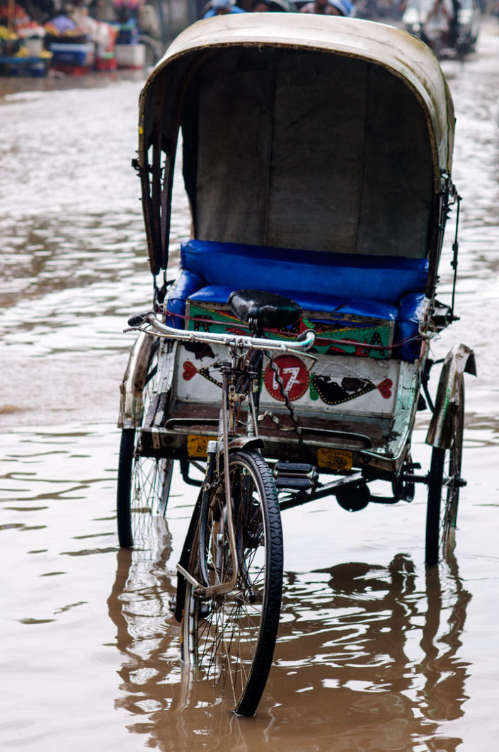 A rickshaw stands in a flooded street in India