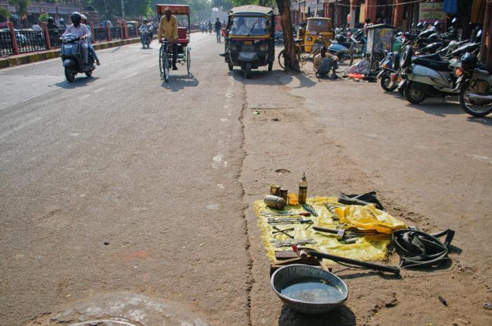 A sidewalk flat tire repair shop in India.