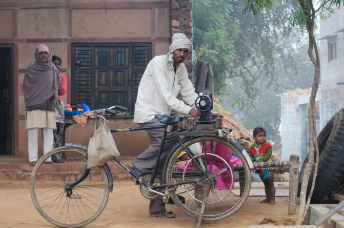 A bicycle powers a sewing machine in India.