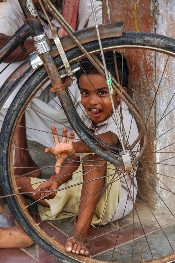 An Indian boy twangs bicycle spokes