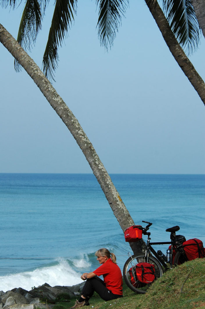 A Western cyclist sits looking out over the sea with their touring bicycle leaned against a palm tree in India.