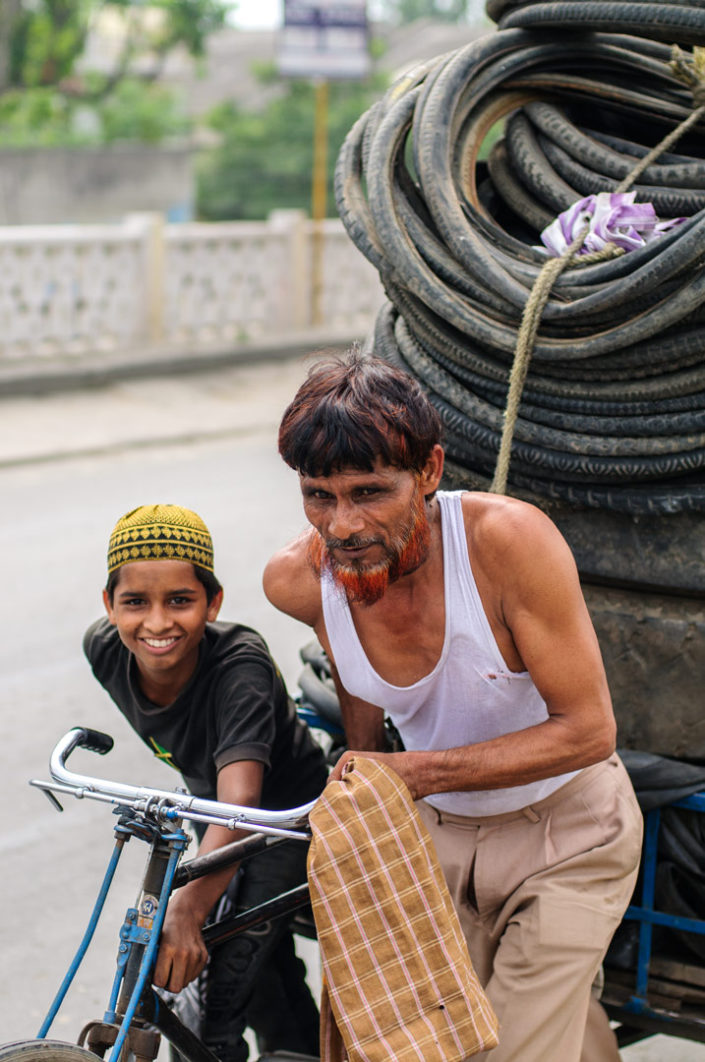 A father and son push a rickshaw loaded with bicycle tires.