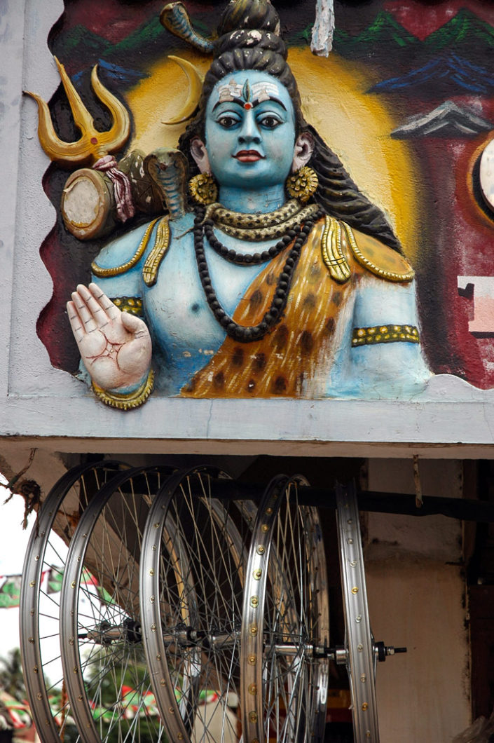 The Indina God Shiva stands above hanging bicycle wheel rims