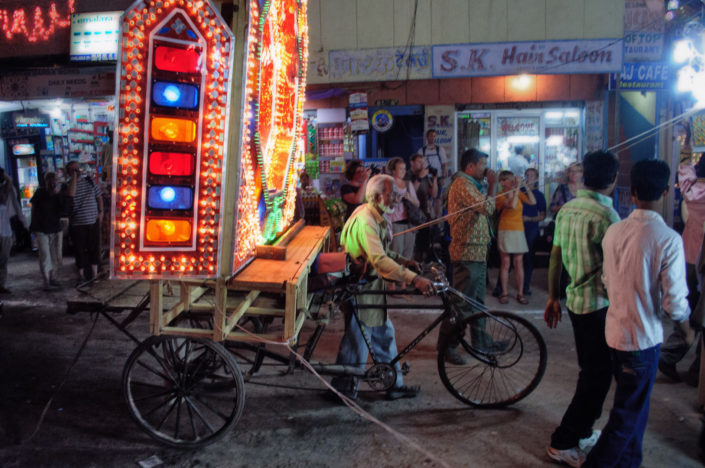 A lighted wedding rickshaw is being pushed during a wedding procession.