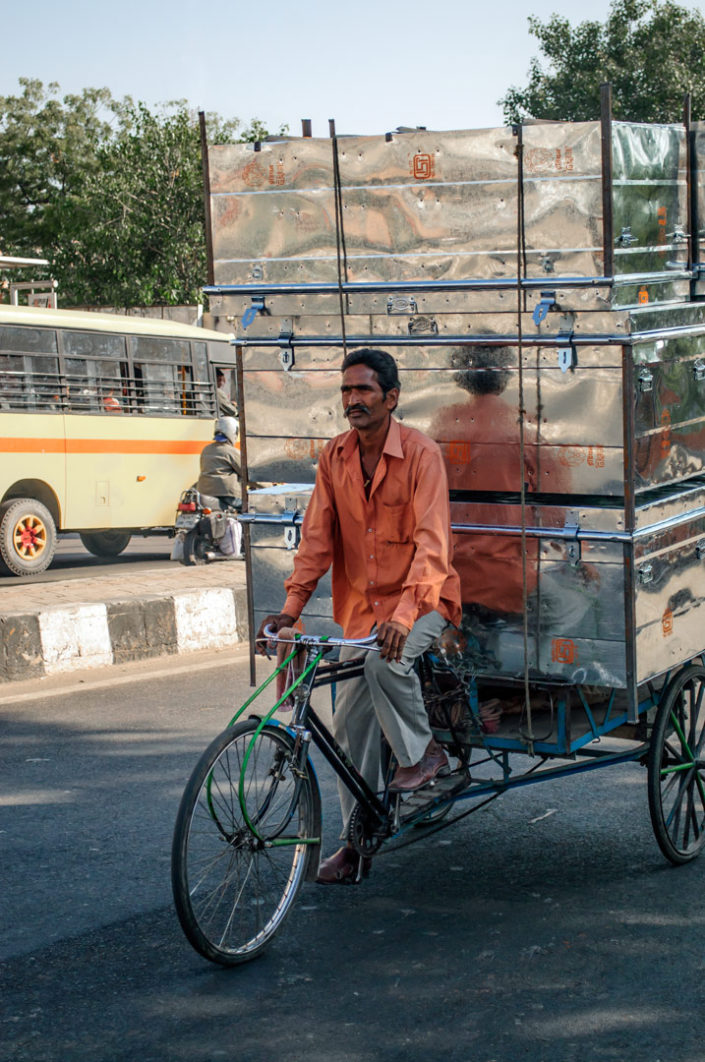 A rickshaw loaded with met cans in India
