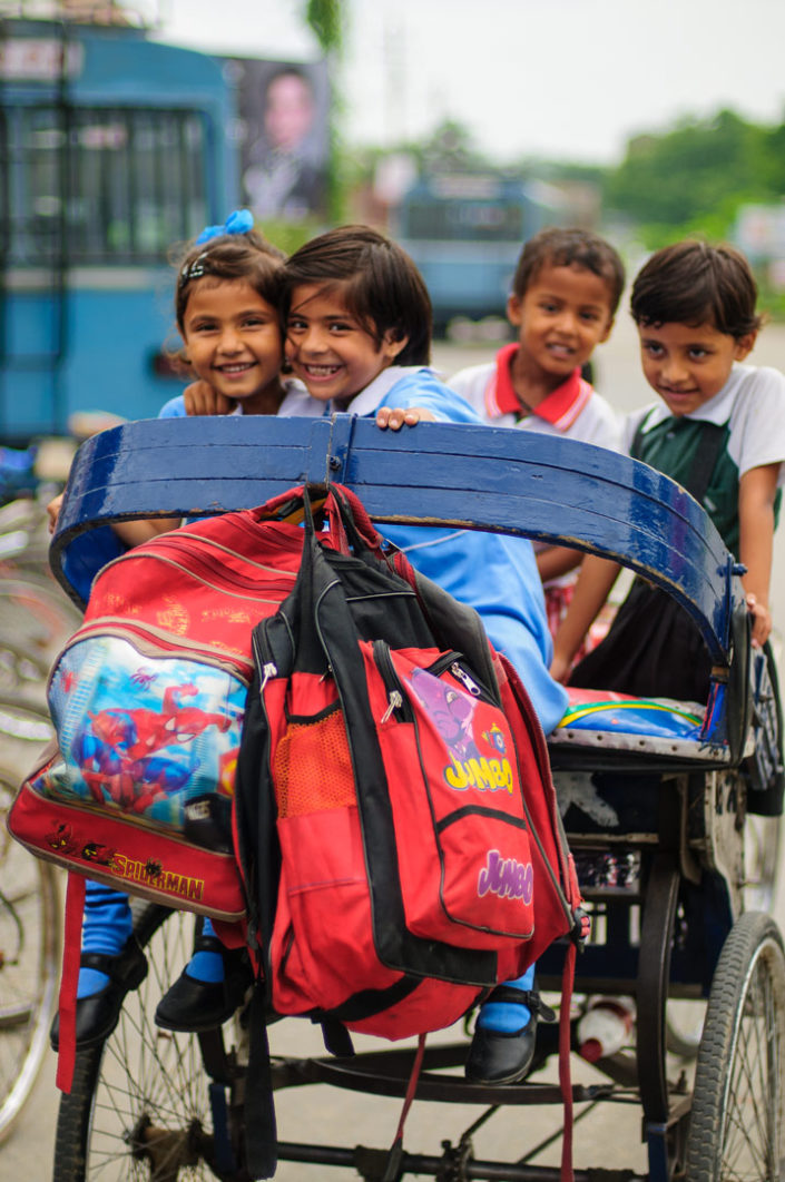 A rickshaw is loaded full of school children in India.