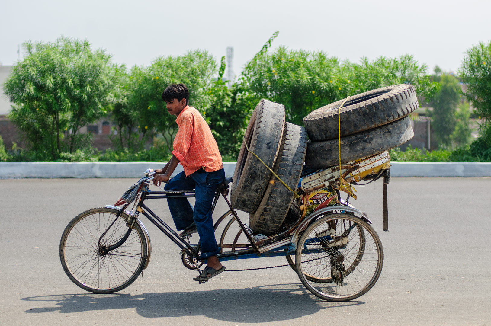 A rickshaw is loaded full of truck tires in North India.