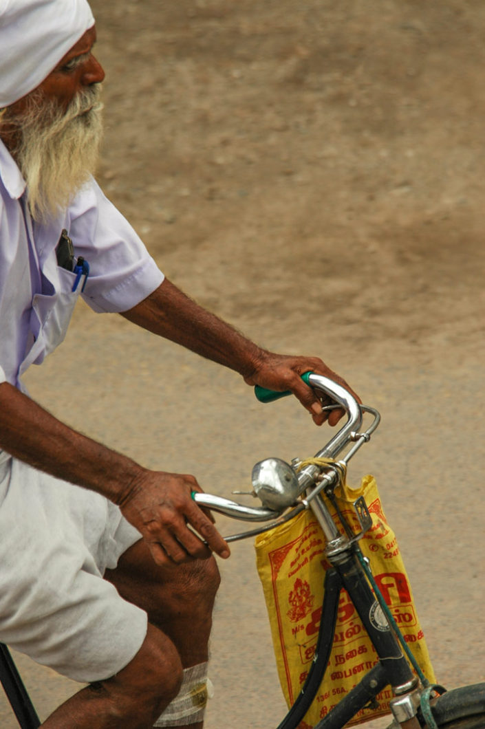 An elderly Sikh pedals his bike