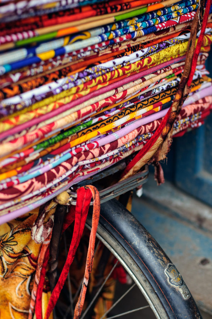 A bicycle rack is loaded with brightly colored material in Nepal