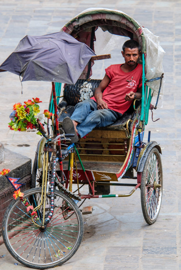 A chauffeur sits in his rickshaw in Kathmandu, Nepal