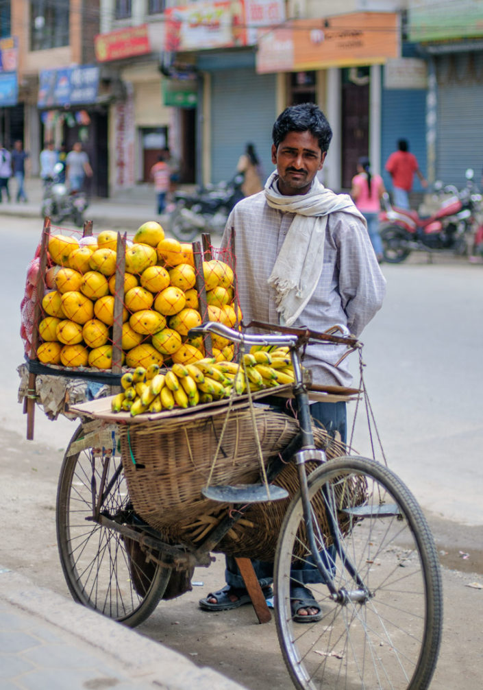 A cycling fruit salesman in Nepal