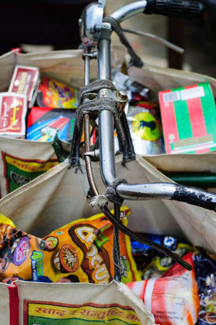 Shopping bags are hung over bicycle handlebars in Nepal.