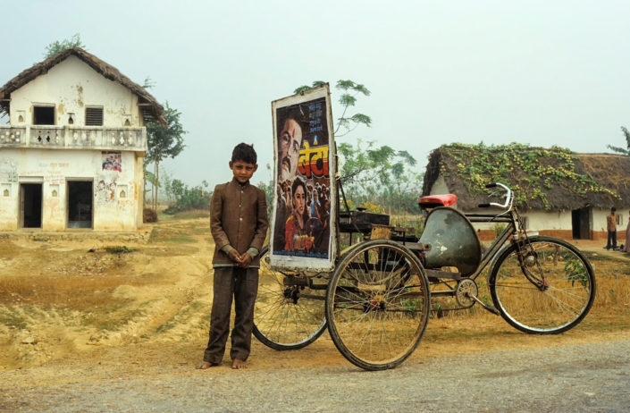 a rickshaw advertises a bollywood film in Nepal.