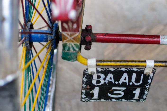 A brightly painted rickshaw wheel and license plate in Nepal