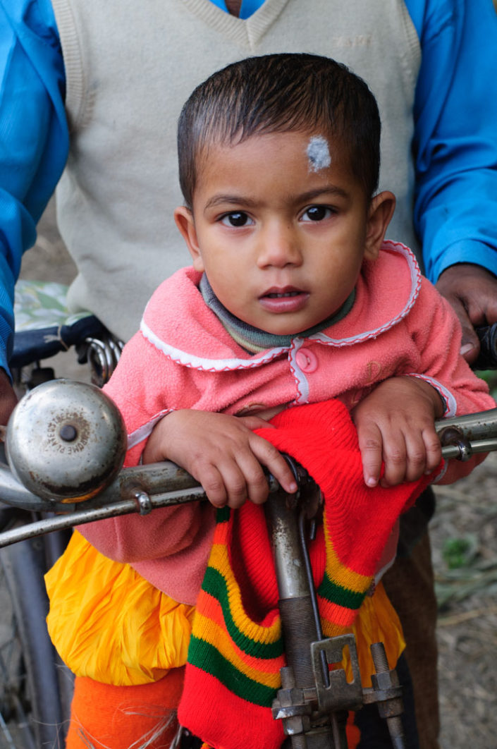 A father and his child sit on a bicycle in Bangladesh