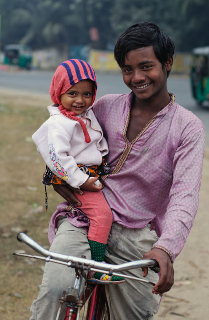 A boy and his little brother sit on a bicycle in Bangladesh