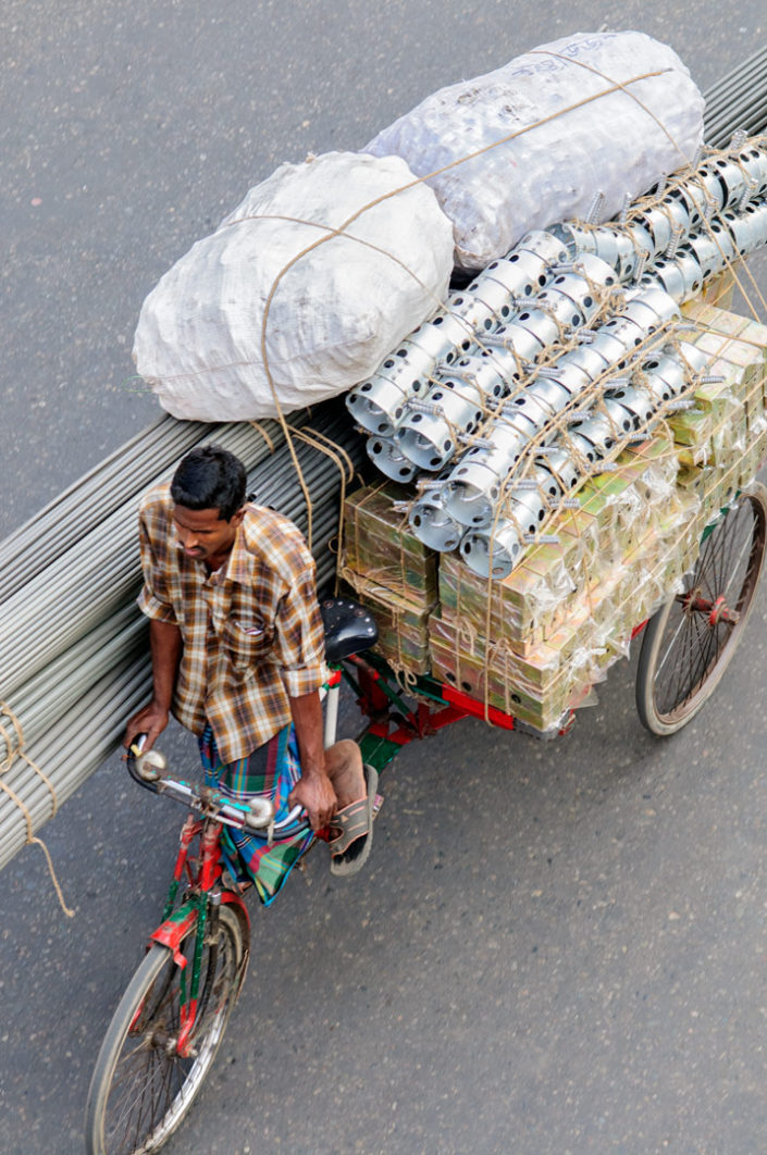 A Bike rickshaw heads to his destination with a full load.