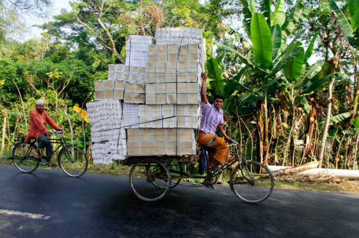 A bike rickshaw in Bangladesh is loaded with boxes