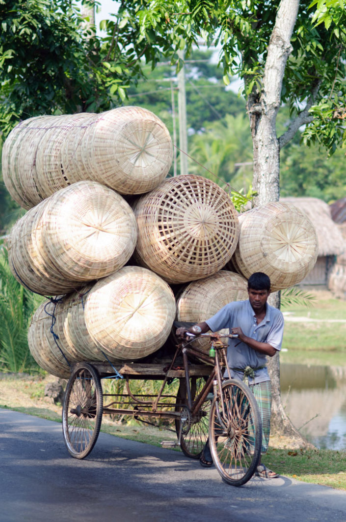 A bike rickshaw is overloaded with large basckets in Bangladesh