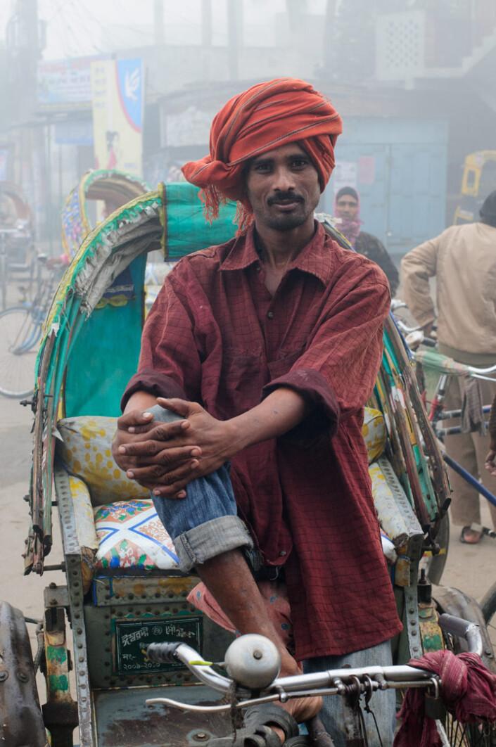 A Bangladesh chauffeur sits in his rickshaw