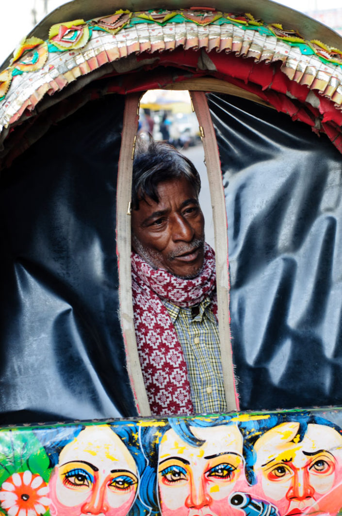 A Bangladesh peers through a rickshaw awning