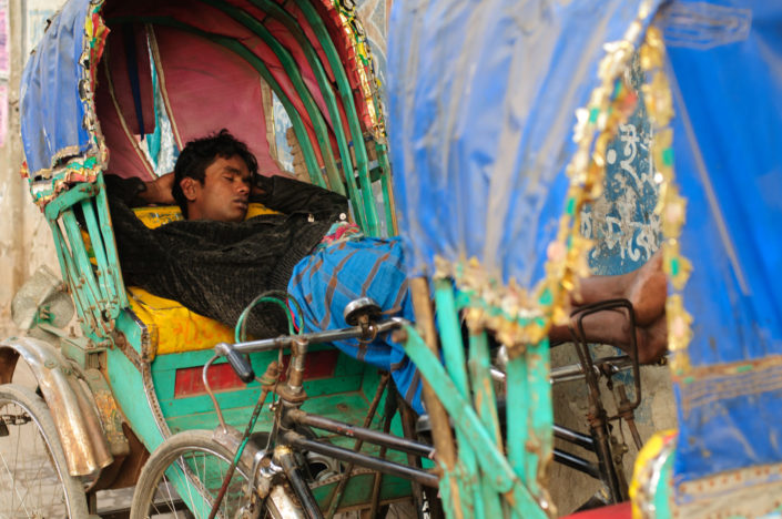 A Bangladesh chauffeur sleeps in his rickshaw
