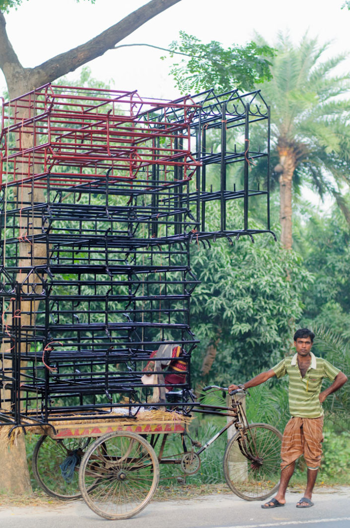 A rickshaw is piled high with metal frames in Bangladesh.