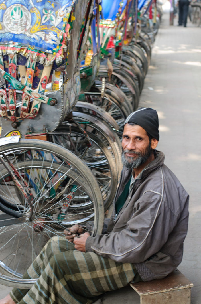 A chauffeur repairs his rickshaw in Dhaka