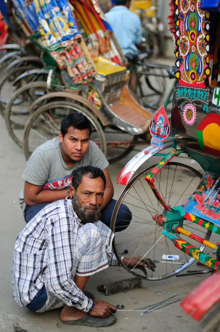 Rickshaw chauffeurs repair a rickshaw in Dhaka.