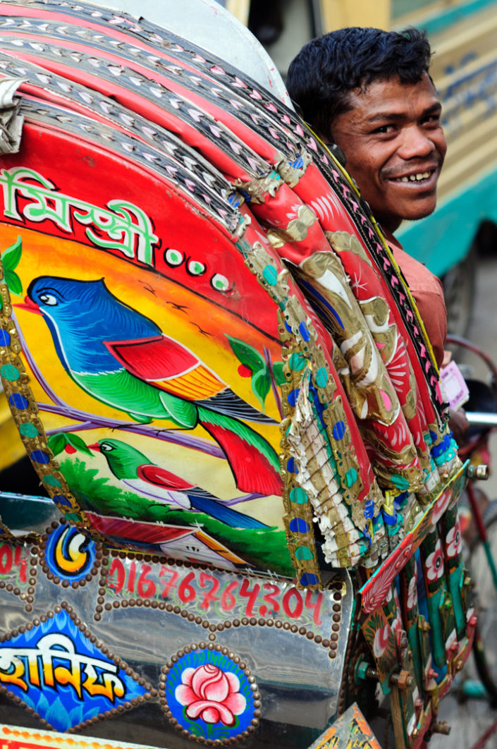 A Dhaka rickshaw chauffeur laughts