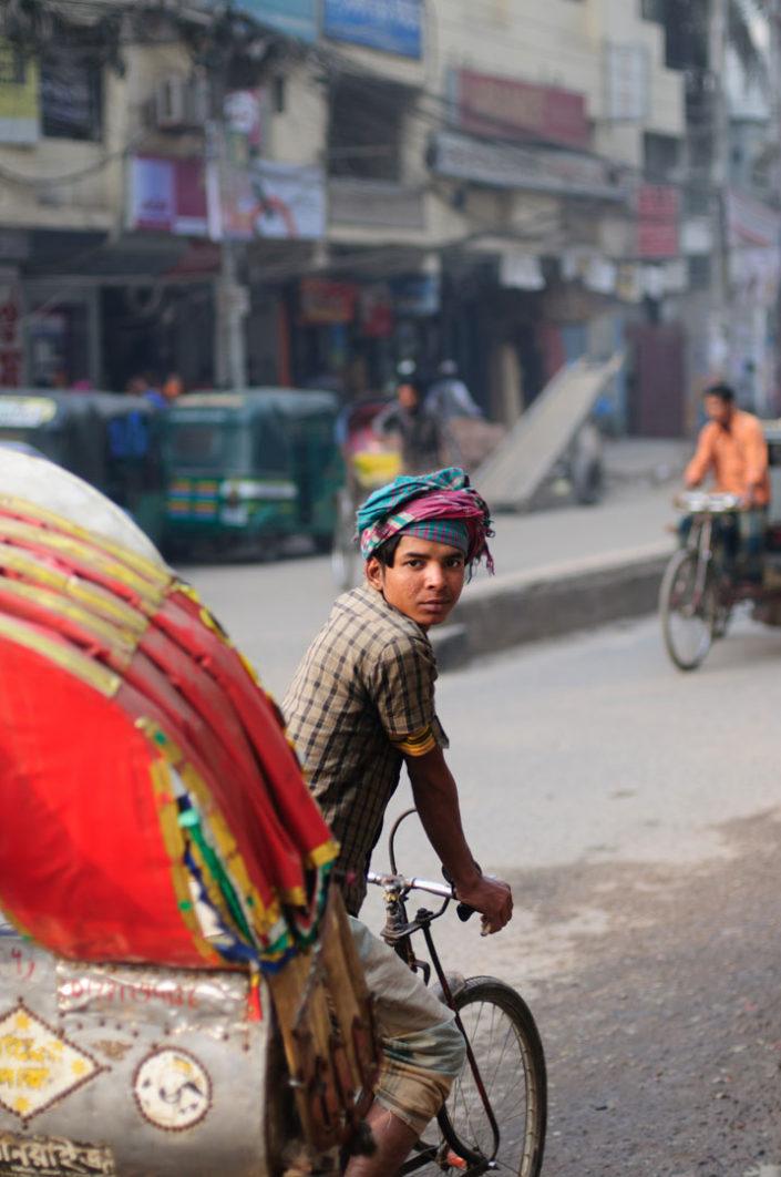 A Dhaka rickshaw chauffeur glances back