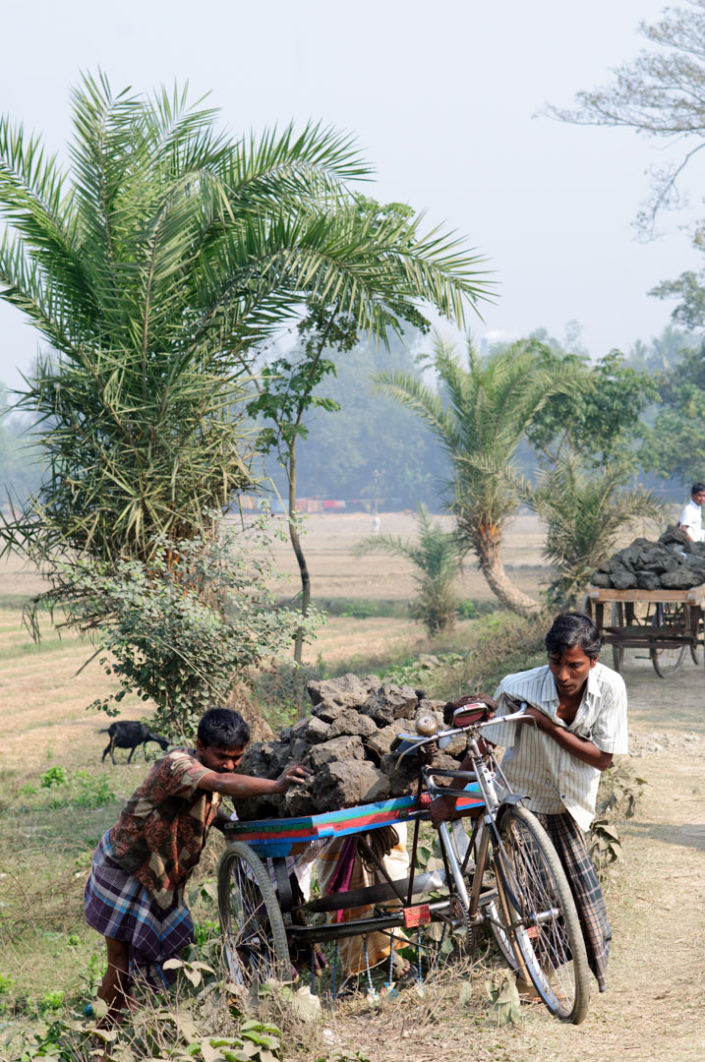 Bangladesh men push van rickshaws loaded with heavy clay