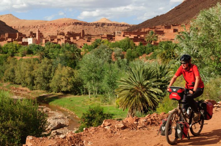 Cycling past a desert oasis in Southern Morocco