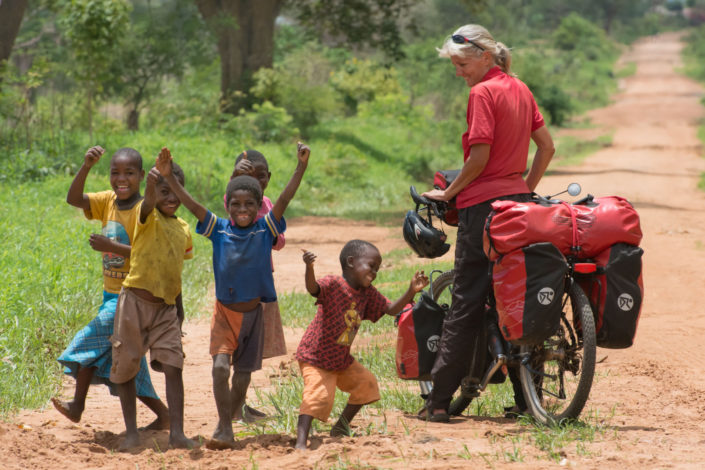 A touring bicyclist views local kids in Malawi, Africa.