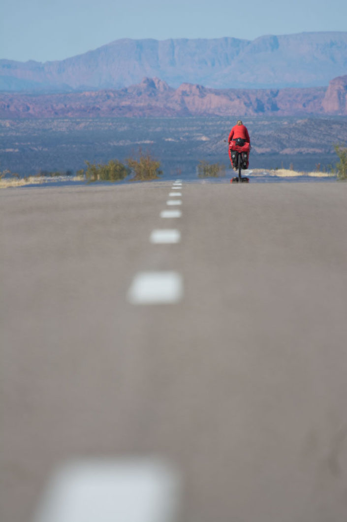 A touring cyclist heads towards colorful rock formations on Ruta 40 in Northern Argentina.