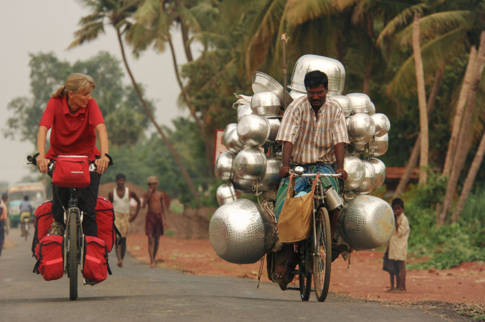A western bicyclist cycles alongside a water can salesman in the state of Tamil Nadu, India