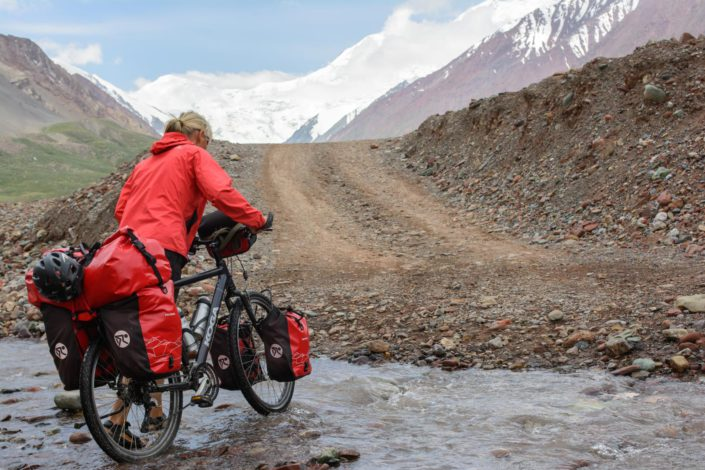 A red touring cyclist pushes their fully loaded bike through a creek near the border of Kyrgyzstan.