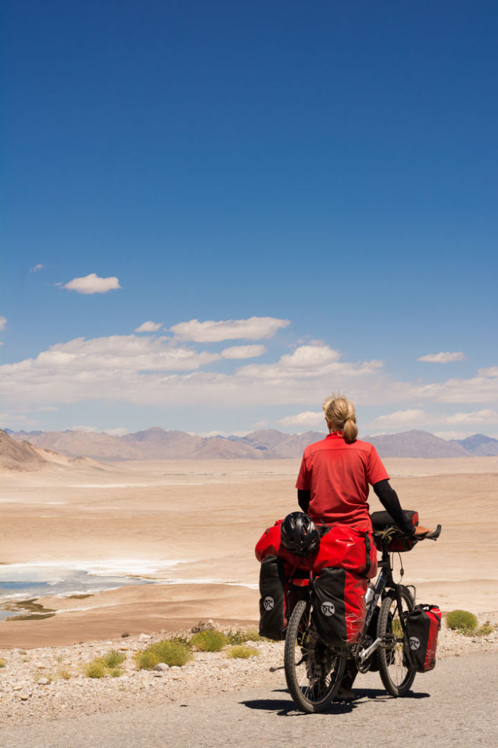 Touring cyclist looks out over the desert in Tajikistan.